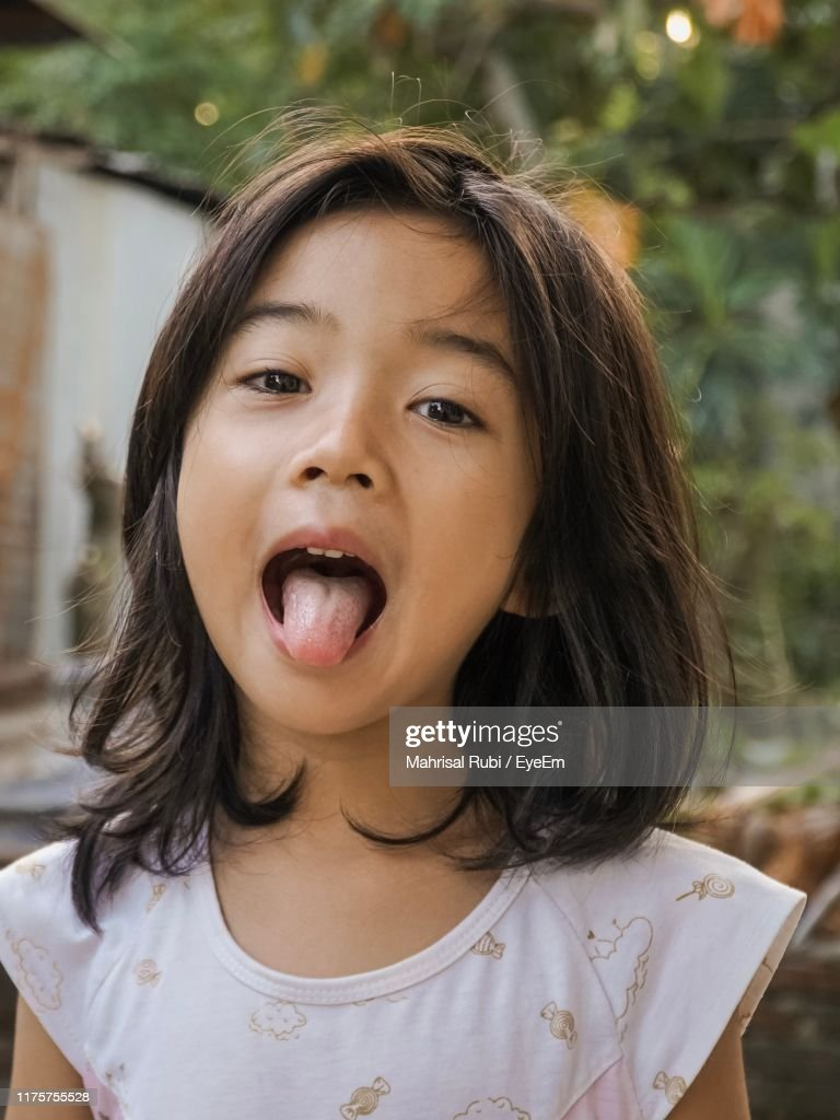 Portrait Of Cute Girl Sticking Out Tongue While Standing