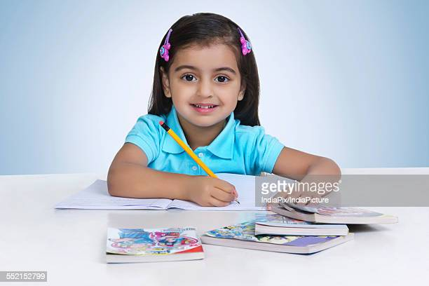 Portrait of cute girl studying against blue background