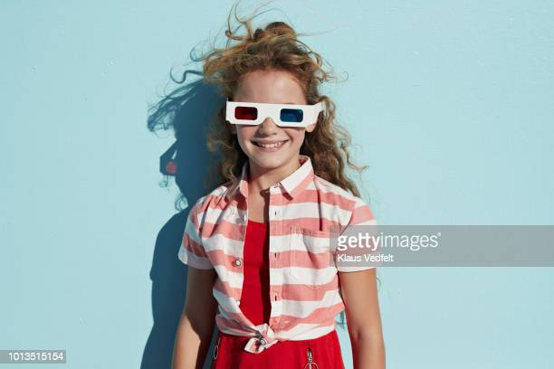 Portrait of cute girl wearing 3D glasses, on studio background