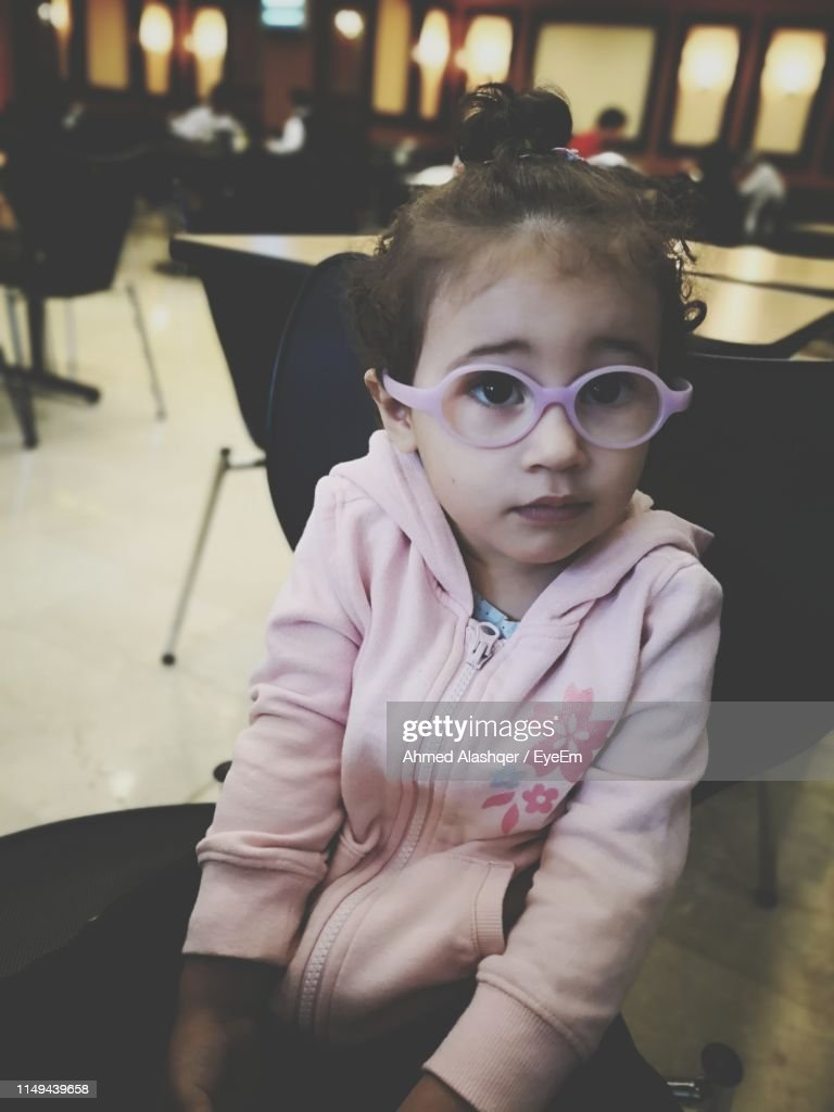 05d97efac9 Portrait Of Cute Girl Wearing Eyeglasses While Sitting In Restaurant :  Stock Photo