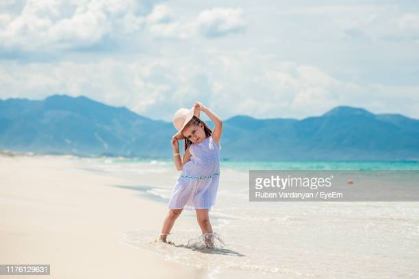 portrait of cute girl wearing hat while standing at beach - ruben vardanyan stock pictures, royalty-free photos & images