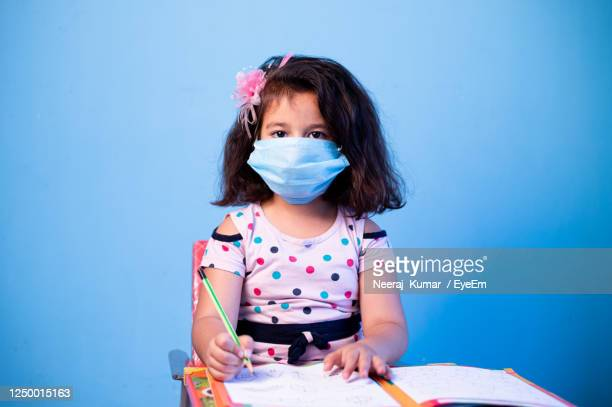 portrait of cute girl wearing mask while doing homework against blue wall - children only stock pictures, royalty-free photos & images