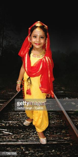 portrait of cute girl wearing salwar kameez standing on railroad track - salwar kameez stock pictures, royalty-free photos & images