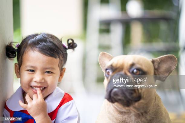 portrait of cute girl with dog - phichet ritthiruangdet stock photos and pictures
