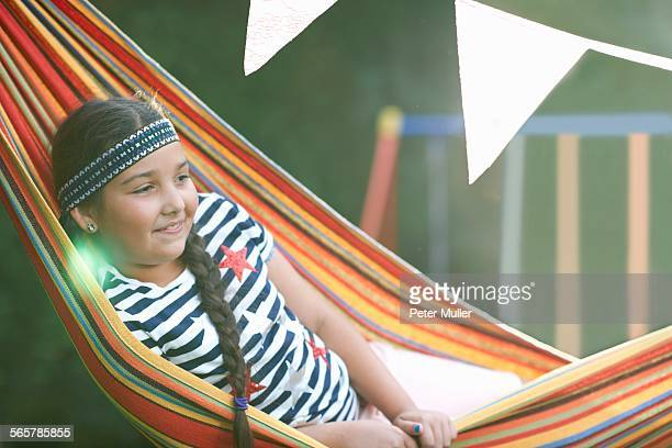 Portrait of cute girl with hairband and plait reclining in striped garden hammock