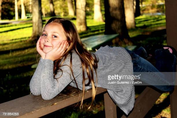 Portrait Of Cute Girl With Hands On Chin Lying On Wooden Bench At Park