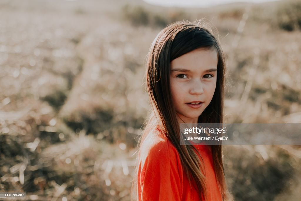 Portrait Of Cute Girl With Long Hair Standing On Field : ストックフォト