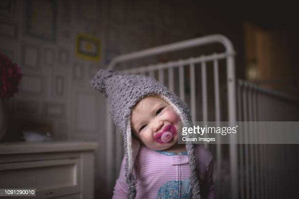portrait of cute girl with pacifier in mouth standing against crib at home - panoramica verticale foto e immagini stock