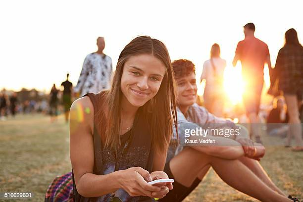 Portrait of cute girl with smartphone at festival