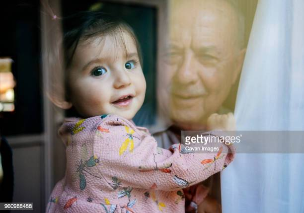 portrait of cute granddaughter carried by grandfather seen through window - photographed through window stock pictures, royalty-free photos & images