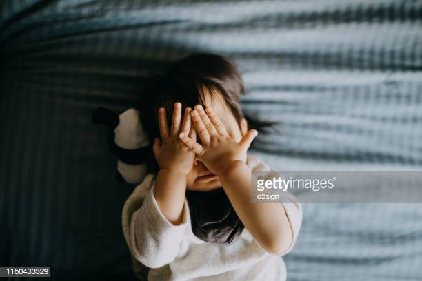 portrait of cute little asian toddler girl covering her face playing peekaboo while lying on bed with panda soft toy lying next to her - augen zuhalten stock-fotos und bilder