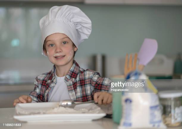 portrait of cute little boy preparing cookies mixing ingredientes while facing camera smiling - chef's hat stock pictures, royalty-free photos & images