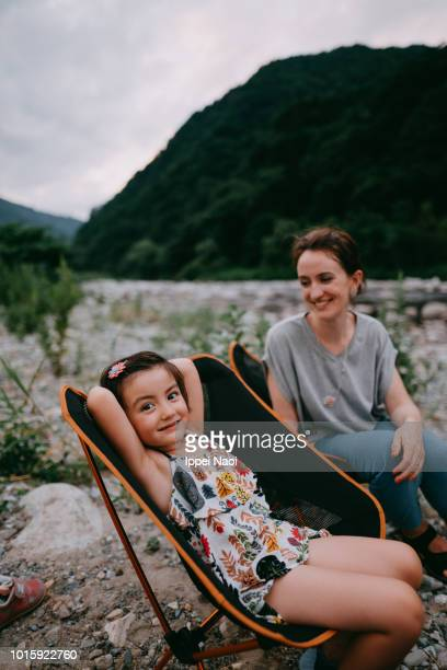 Portrait of cute little girl and mother sitting in camping chair and smiling, Japan