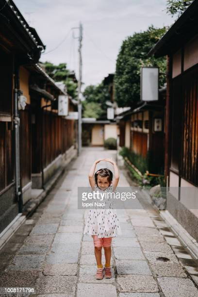 Portrait of cute little girl dancing in old street in Kyoto, Japan