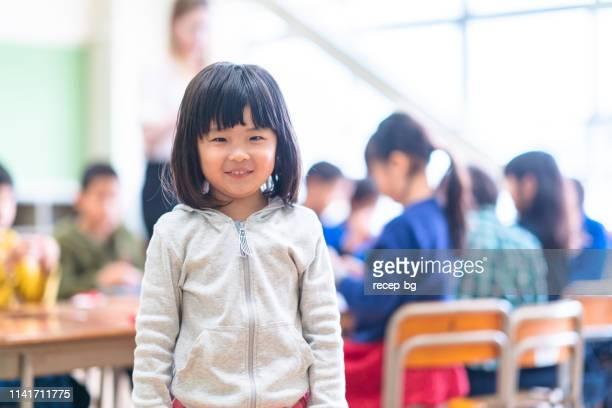 教室でかわいい女の子の肖像 - 幼稚園児 ストックフォトと画像