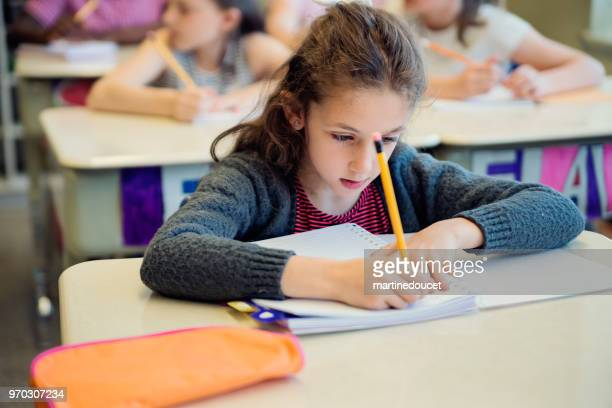 Portrait of cute little girl in classroom, working at her desk.