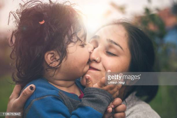 portrait of cute little girl kissing her mom - indian girl kissing stock photos and pictures