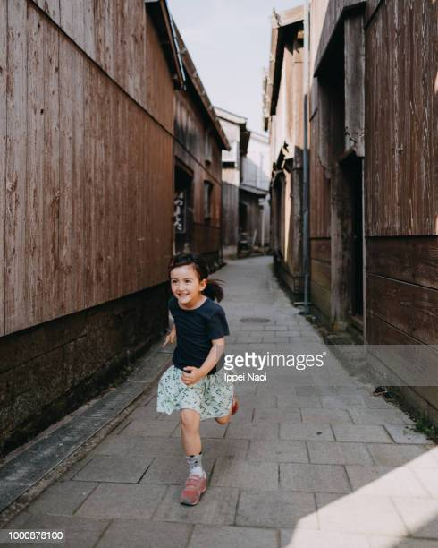Portrait of cute little girl running with smile in old Japanese village