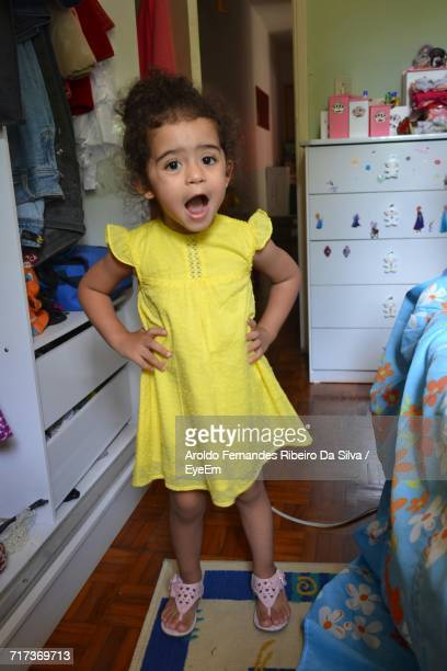 Portrait Of Cute Little Girl Standing By Cabinet At Home