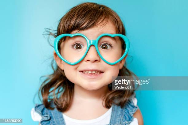 portrait of cute little girl with heart shaped glasses on blue background - portrait blue background stock pictures, royalty-free photos & images