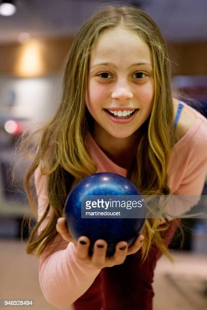 Portrait of cute long hair preteen girl playing bowling.
