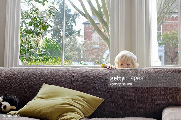 portrait of cute male blond toddler hiding behind sofa - escondendo - fotografias e filmes do acervo