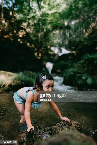 Portrait of cute mixed race little girl playing in river water in forest
