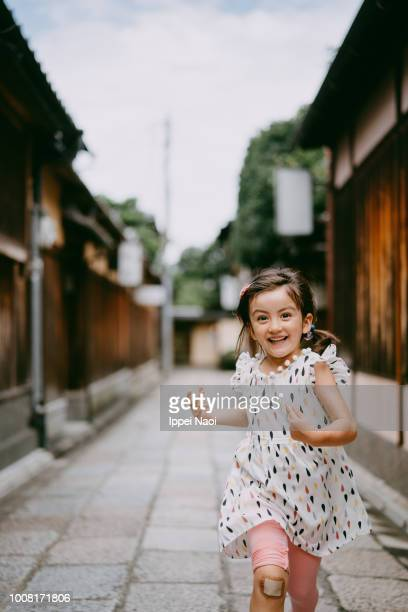 Portrait of cute mixed race little girl running with smile in Kyoto, Japan