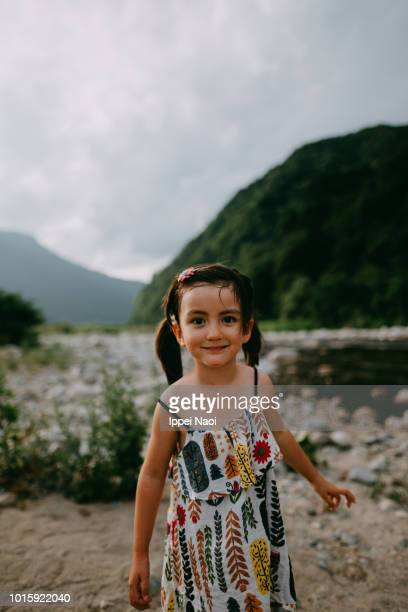 Portrait of cute mixed race little girl smiling at camera by river