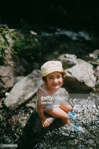 Portrait of cute mixed race little girl smiling at camera while playing in river water