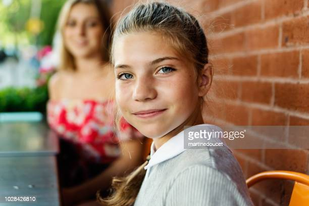 Portrait of cute preteen girl outdoors on a brick wall.