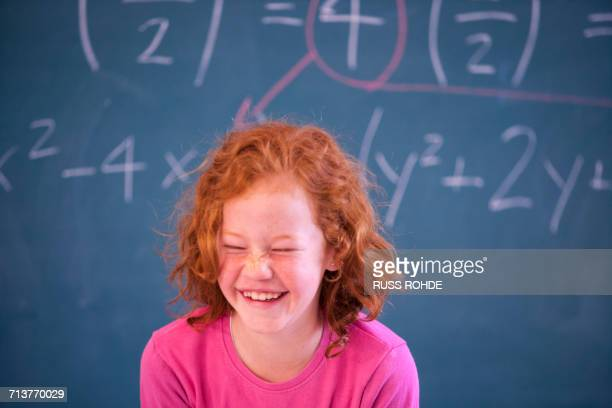 portrait of cute primary schoolgirl giggling in classroom - free images for educational use stock pictures, royalty-free photos & images