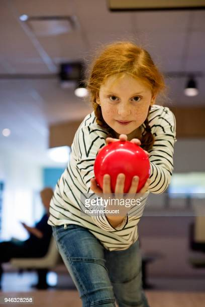 Portrait of cute redhead preteen girl playing bowling.