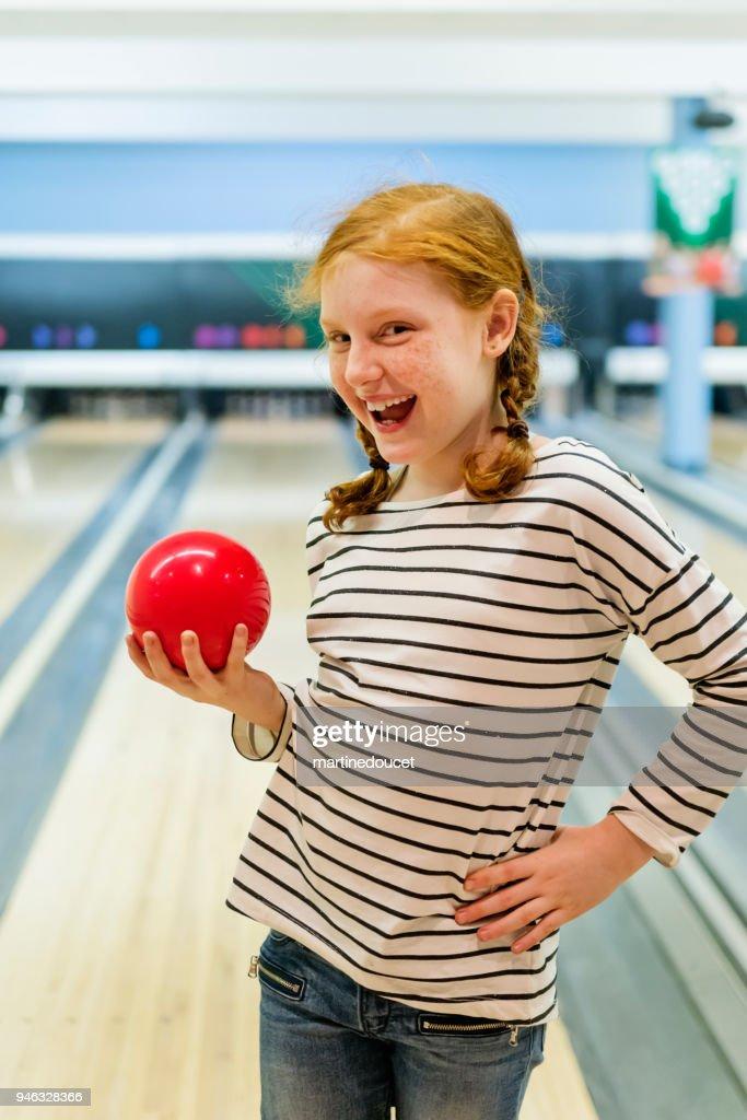Portrait of cute redhead preteen girl playing bowling. : Stock Photo