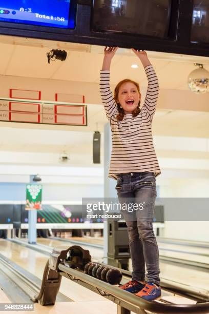 Portrait of cute redhead preteen girl playing bowling.