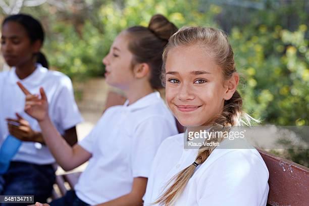 Portrait of cute schoolgirl among her friends