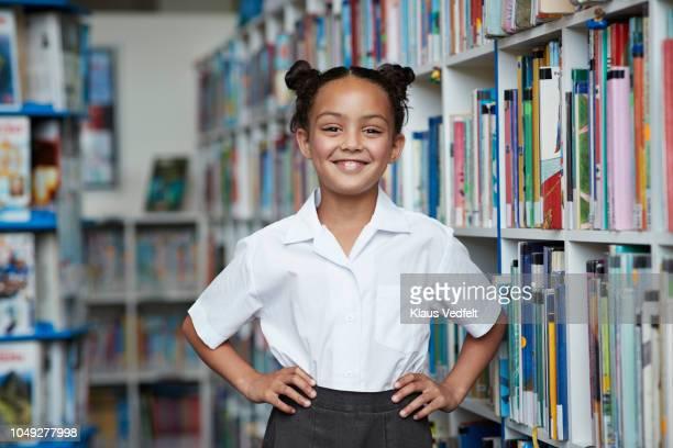 portrait of cute schoolgirl at the library - 8 9 años fotografías e imágenes de stock