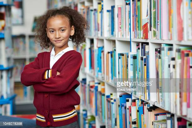 portrait of cute schoolgirl at the library - determination stock pictures, royalty-free photos & images