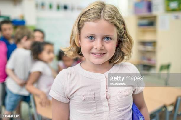 Porträt der niedliche Schulmädchen lächelnd im Klassenzimmer
