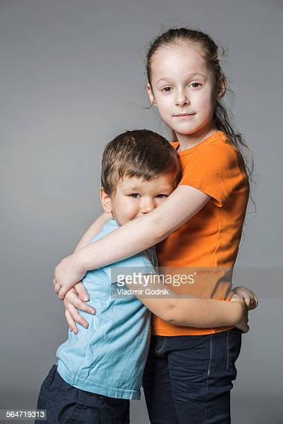 Portrait of cute siblings embracing against gray background