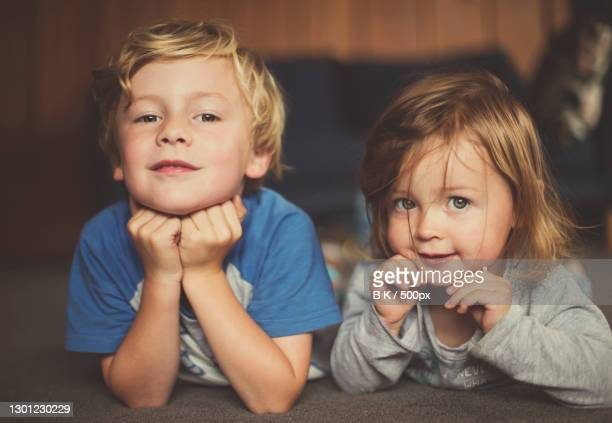 portrait of cute siblings lying on bed at home,christchurch,canterbury,new zealand - images stock pictures, royalty-free photos & images