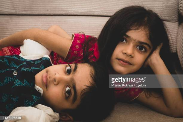 portrait of cute siblings lying on sofa at home - indian culture stock pictures, royalty-free photos & images