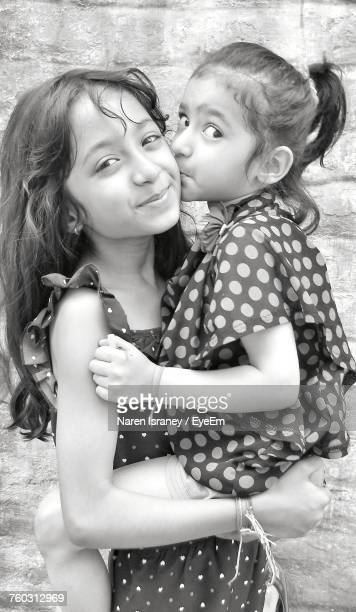 portrait of cute sisters - indian girl kissing stock photos and pictures