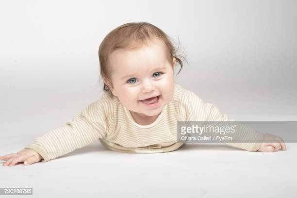 Portrait Of Cute Smiling Baby Girl Lying On White Background