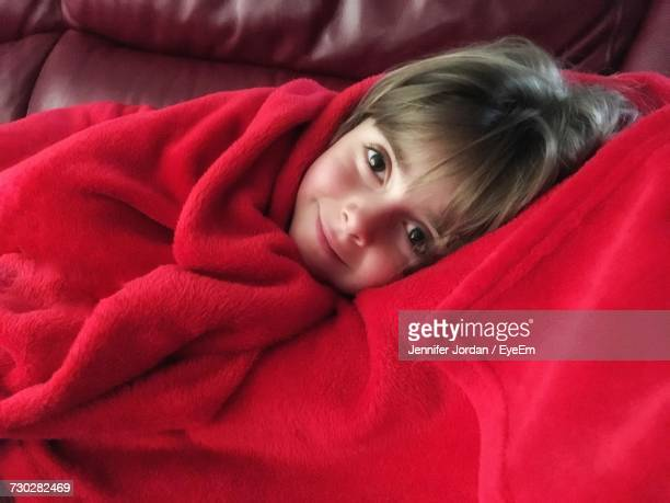 Portrait Of Cute Smiling Girl Covered With Red Blanket While Lying On Sofa At Home