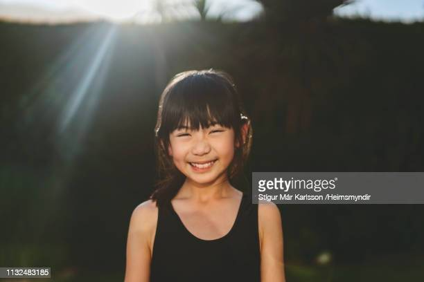 portrait of cute smiling girl in yard on sunny day - bangs stock photos and pictures