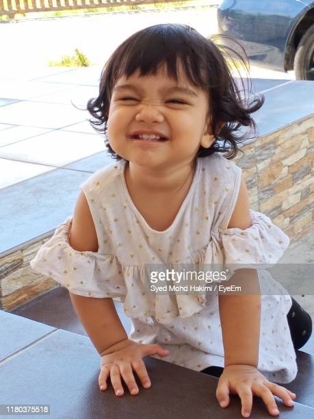 portrait of cute smiling girl sitting on steps - hakimi stock photos and pictures