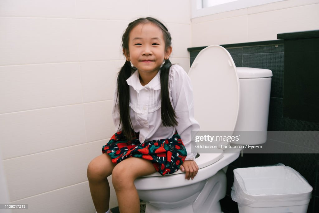 Woman Sits On Toilet Bowl In The Bathroom, Bottom View