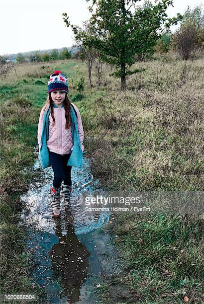 portrait of cute smiling girl standing on water amidst grassy field - innocence stock pictures, royalty-free photos & images