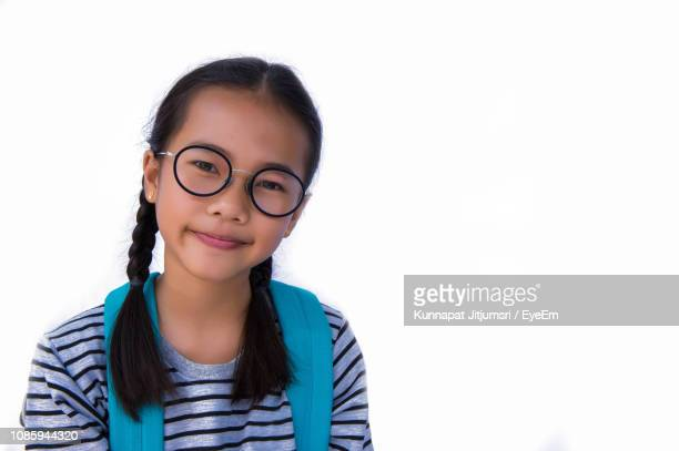 portrait of cute smiling girl wearing eyeglasses against white background - very young thai girls stock photos and pictures